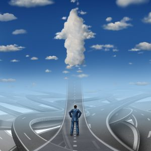 Career development business concept as a businessman standing in front of a group of tangled roads and streets with one straight highway leading to an arrow cloud as a metaphor.
